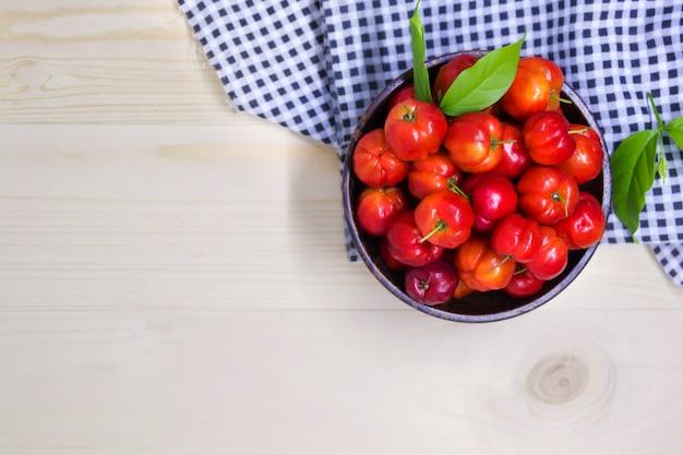 Bagas da cereja doce na bacia de madeira com tela da tartã na tabela, alimento saudável da fruta.
