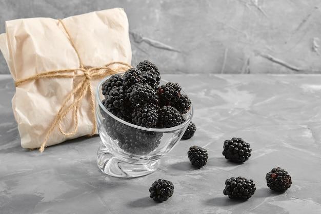 Bagas de amora madura close-up, sobre um fundo cinza entrega de produtos, cópias do espaço, fotos para o catálogo de lojas.