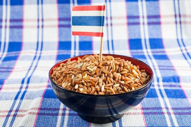 Bagas de arroz integral tailandês no tecido tailandês de fundo, bandeira da tailândia