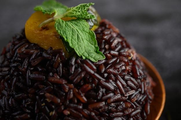 Bagas de arroz roxo cozido em um prato de madeira com folhas de hortelã e abóbora.