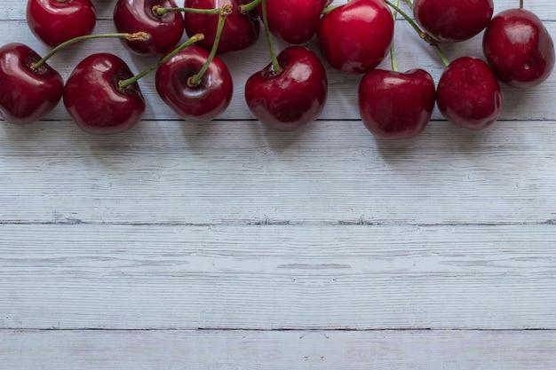 Bagas de cereja em uma vista superior do plano de fundo de madeira