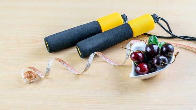 Bagas de cereja no prato, fita dosadora e corda de pular como símbolos do esporte e da nutrição balanceada. conceito de estilo de vida saudável.