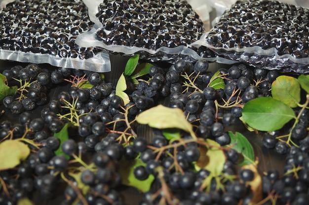 Bagas de chokeberry (aronia melanocarpa) são embaladas em sacos a vácuo e bagas pretas na mesa escura.