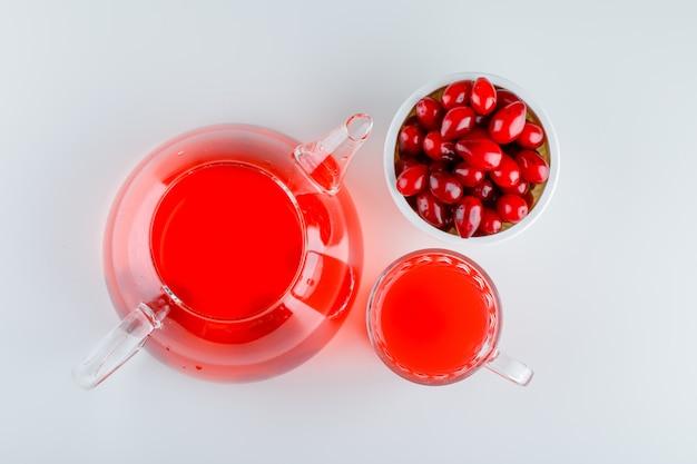 Bagas de cornel em uma tigela com bebida em branco
