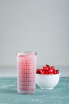 Bagas de cornel em uma tigela com vista lateral para bebida em gesso e branco