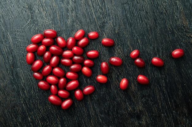 Bagas de dogwood vermelhas em forma de coração partido na superfície de madeira preta