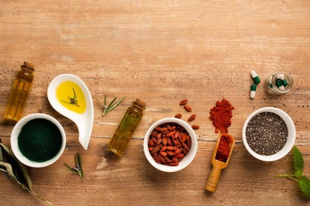 Bagas de goji de vista superior com óleo e remédio em cima da mesa