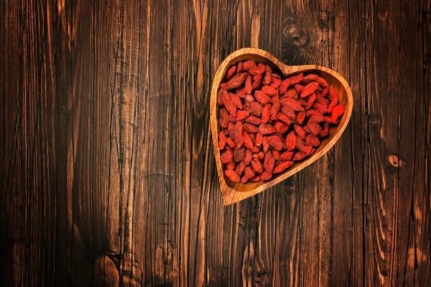 Bagas de goji em uma tigela de madeira em forma de coração sobre fundo de madeira.