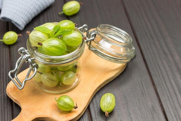 Bagas de groselha verde em frasco de vidro e na placa de madeira. berry na mesa. vista do topo. fundo de madeira.