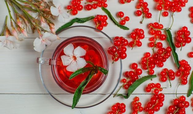 Bagas de groselha vermelha com folhas, chá, flores na madeira.
