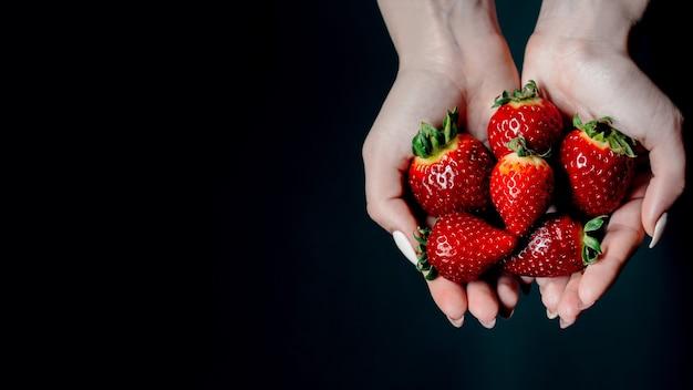 Bagas de morango maduras nas mãos das mulheres. espaço para o seu texto