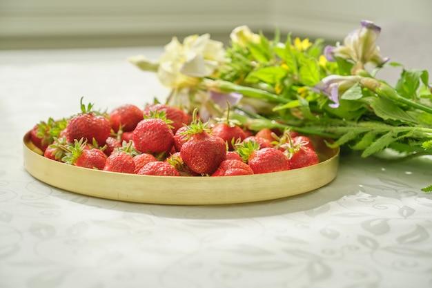 Bagas de morango maduro vermelho na mesa branca na bandeja de ouro