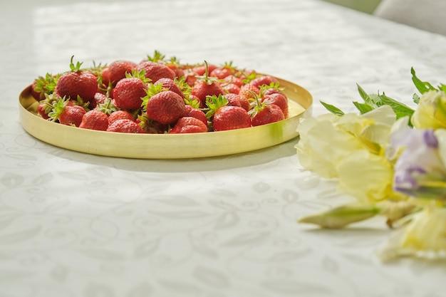 Bagas de morango vermelho maduro na mesa branca na bandeja dourada, vitaminas naturais na primavera, alimentação saudável. buquê de flores perto de morangos