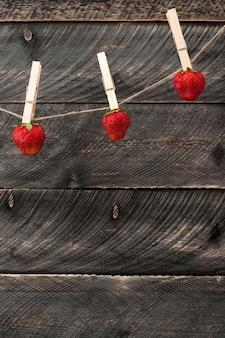 Bagas de morangos frescos de verão com pino pendurado em um varal em um fundo escuro de madeira