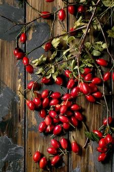Bagas de rosa mosqueta com galho e folhas no antigo fundo de prancha de madeira escura. reservas de vitaminas de outono para o inverno. postura plana, copie o espaço
