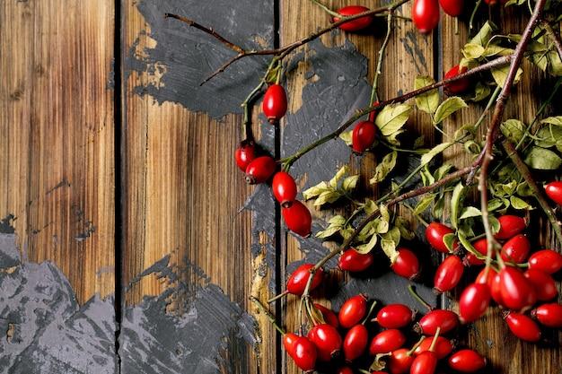 Bagas de rosa mosqueta com galho e folhas no fundo de prancha de madeira velha. reservas de vitaminas de outono para o inverno. postura plana, copie o espaço