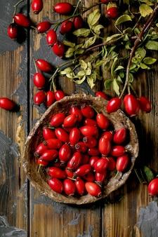 Bagas de rosa mosqueta na placa de cerâmica com galho e folhas no fundo de prancha de madeira velha. reservas de vitaminas de outono para o inverno. cama plana, close-up