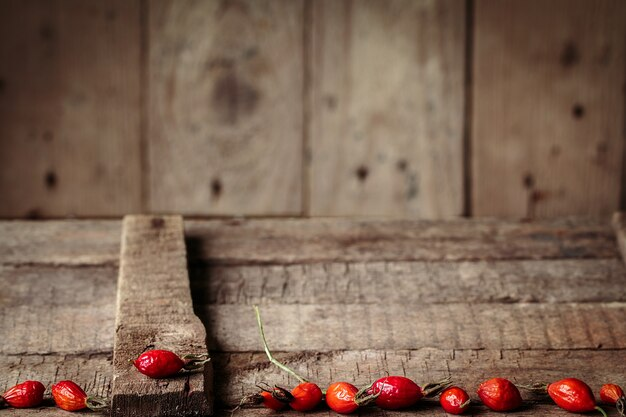 Bagas de uma rosa brava em uma mesa de madeira