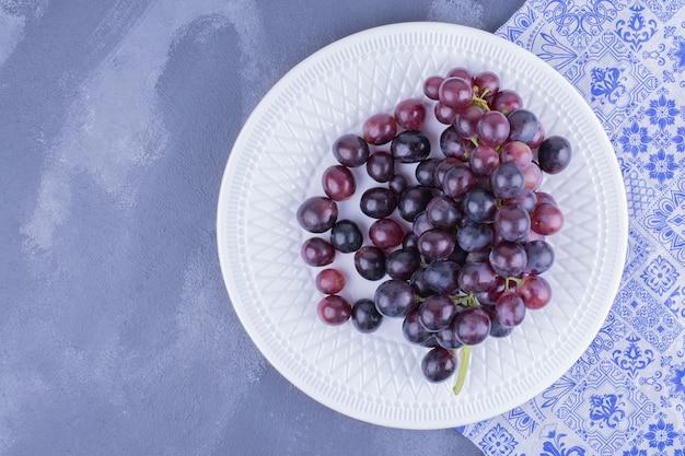 Bagas de uva vermelha em um prato branco.