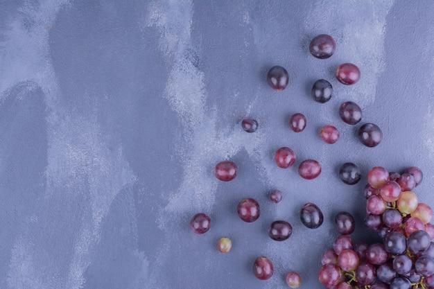 Bagas de uva vermelha isoladas na mesa azul.