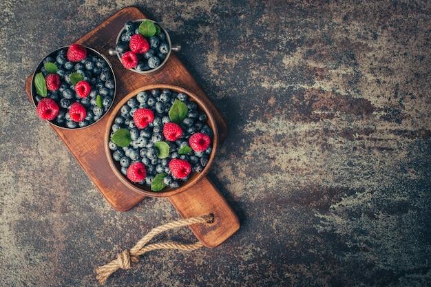 Bagas de verão misturam-se com framboesa, mirtilo em pratos de madeira e metal.