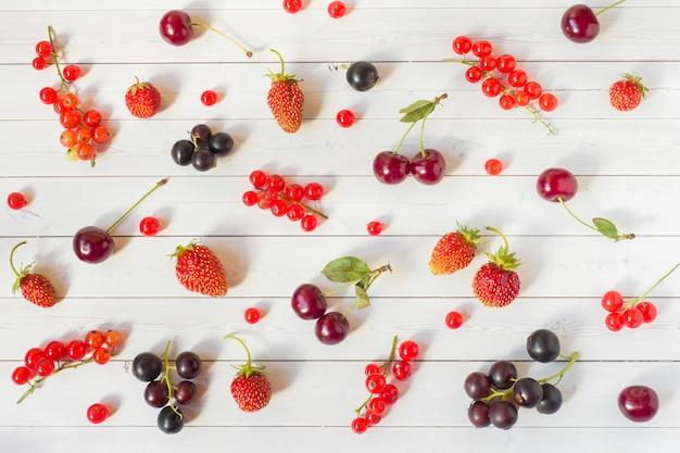 Bagas de verão morangos, groselhas e cerejas na mesa branca