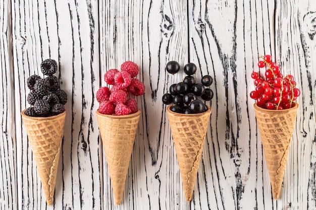 Bagas de verão no cone waffle em fundo branco de madeira