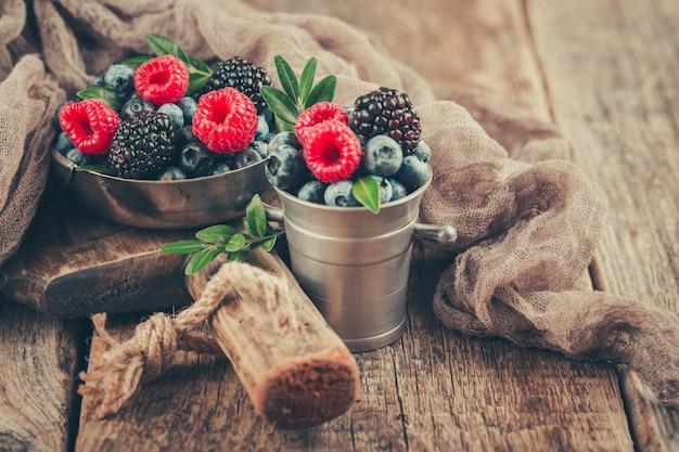 Bagas de verão se misturam com framboesa, mirtilo e amora preta em pratos de metal sobre fundo de madeira