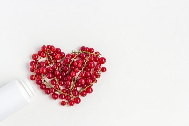 Bagas de vitaminas frescas como forma de coração do frasco de comprimidos de medicamento branco.