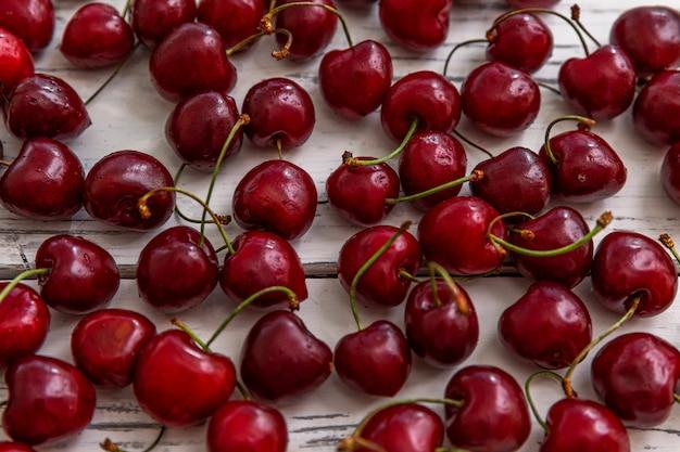 Bagas dispersas de cerejas maduras sobre um fundo claro de madeira. vista do topo. vitaminas sazonais.