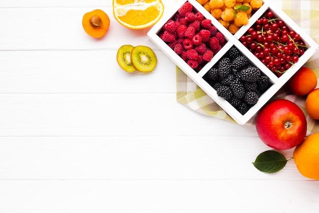 Bagas e frutas frescas flat-lay com espaço da cópia