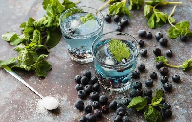 Bagas e hortelã em torno de bebidas refrescantes de mirtilo