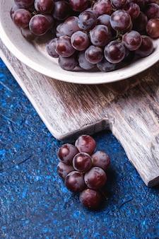 Bagas frescas de uvas maduras em uma tigela de madeira branca e uma velha tábua de corte na mesa abstrata azul, vista de ângulo macro