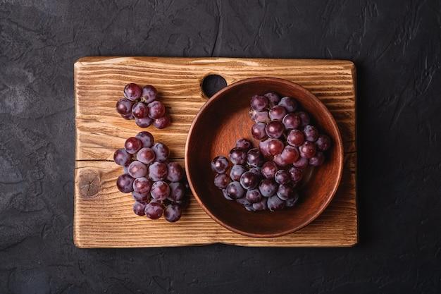 Bagas frescas de uvas maduras em uma tigela de madeira marrom e uma tábua de cortar na superfície de pedra escura