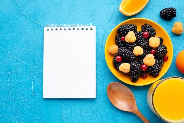 Bagas frescas e frutas planas com bloco de notas
