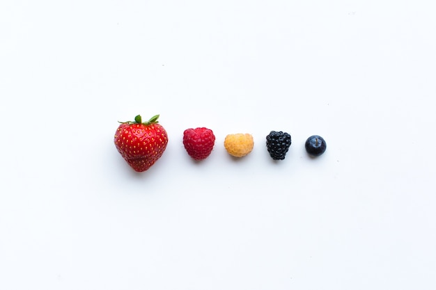 Bagas frescas saudáveis coloridas em uma linha em um fundo branco