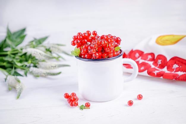 Bagas maduras de groselha em uma xícara branca e flores