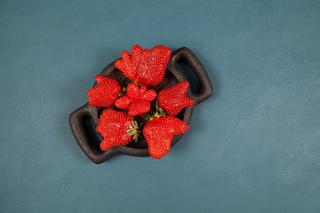 Bagas maduras engraçadas de morango na placa de madeira, vista superior. conceito - redução de resíduos orgânicos.