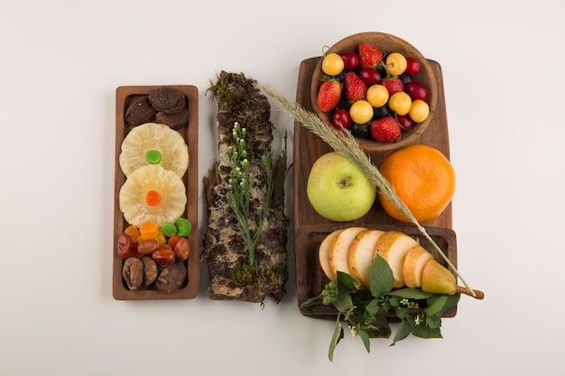 Bagas, mix de frutas e ervas em uma travessa de madeira no centro