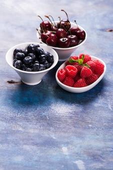 Bagas orgânicas doces: framboesa, mirtilo e cereja em tigelas brancas sobre fundo azul grunge
