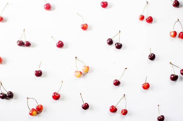 Bagas vermelhas amarelas e escuras de uma cereja doce em um fundo branco