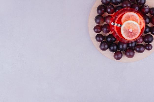 Bagas vermelhas de cereja com um copo de suco em cinza.