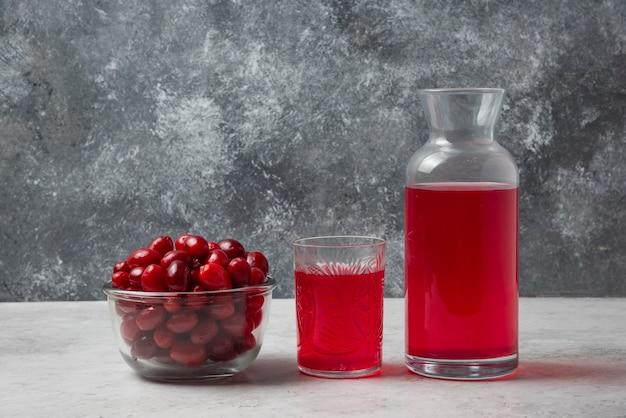 Bagas vermelhas de cornel em um copo de vidro com suco à parte.