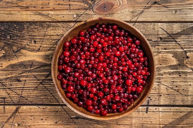 Bagas vermelhas de cranberry em uma placa de madeira. fundo de madeira. vista do topo.