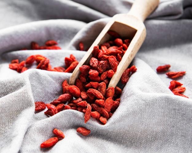 Bagas vermelhas de goji secas para uma dieta saudável em um fundo de tecido
