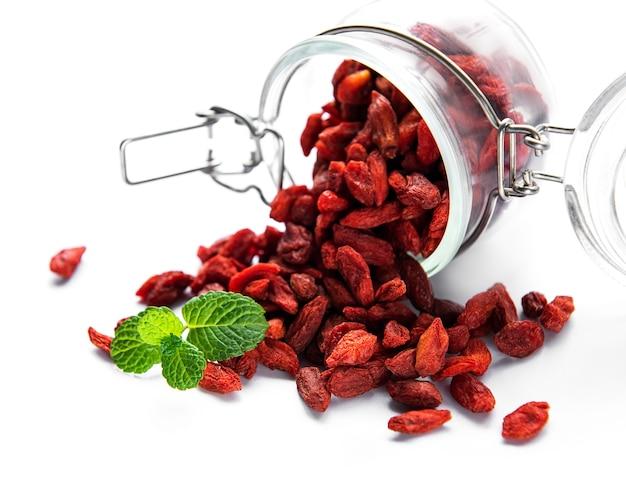 Bagas vermelhas de goji secas para uma dieta saudável em uma superfície branca