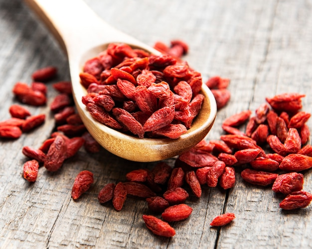Bagas vermelhas de goji secas para uma dieta saudável em uma superfície de madeira velha