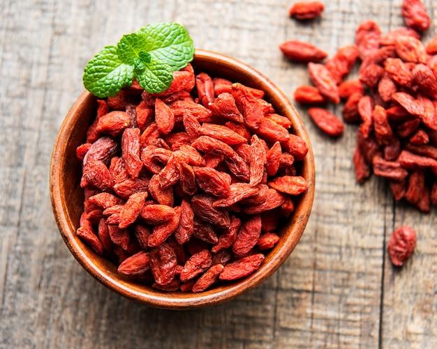 Bagas vermelhas secas de goji para uma dieta saudável em um fundo de madeira velho