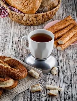 Bagel turco com uma xícara de chá na superfície de madeira, vista de alto ângulo.