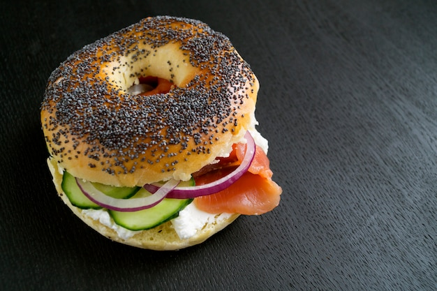 Bagels com cream cheese e salmão defumado em um fundo preto